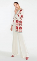 A white ensemble glorified with a red, black and blue patterned patchwork paired with long sleek white bottoms.
