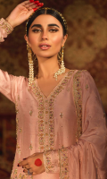 'Nazakat' is a mingling of elegance and tradition. A pure raw silk outfit in blush pink with hints of mauve resham work. The dress is intricately embellished with gold and silver zardoze work with pearls on a floral theme and is paired with handcrafted matching  pure raw silk culottes. It is adorned and finished with banarsi in hues of pink and gota lace, worn with a flowing embroidered blush pink dupatta in medium silk with a hand embellished border and booti. A matching pouch can be made on order to complete the look.