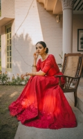 Crimson peshwaz with a huge flare . Hem entirely embroidered with crimson silk thread and embellished with red sequins . Embroidery is also included on the neckline , sleeves and panel joints. Cambric straight trouser in crimson . Zari cotton net dupatta.