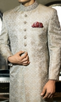 Cotton jamawar fabric sherwani designed with block print all over front panels and sleeve motifs and intricate hand embroidery on collar, sleeves and buttons. Also, highlighted with contrast fabric piping and handkerchief.